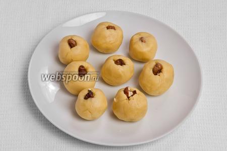 Во внутрь каждого шарика кладём четвертинку ореха и обвалакиваем его тестом.