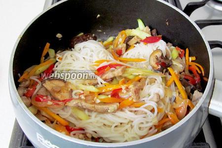 Рисовую лапшу отварить, как написано на упаковке или просто выдержать в кипятке. Добавить лапшу к овощам с мясом и грибами. Прогреть всё вместе 1 минуту. Попробовать на соль.