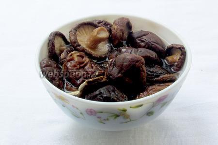 Грибы шиитаке промыть и залить прохладной водой для размягчения. Если ножки у грибов очень твёрдые, то их лучше отрезать. Через 20 минут жидкость слить, а грибы  слегка отварить, минут 5-7. Если использовать свежие грибы шиитаке или шампиньоны, то эти манипуляции можно опустить.