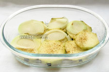 Форму смазать растительным маслом и выложить кружочки баклажан. Посолить, поперчить и посыпать специями. Сверху каждого кружочка выложить лук.