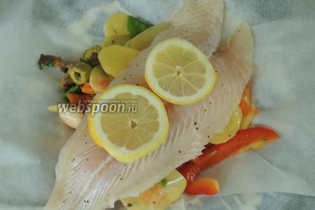 Филе приправим солью и перцем по вкусу, и кладём сверху на овощи, и добавляем кружочки лимона.