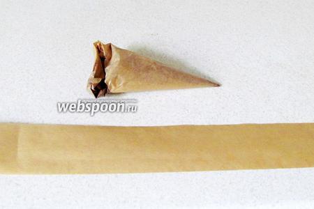 Выложить шоколад в корнетик. Вырезать из пергамента ленту, равную высоте и диаметру торта. Лучше вырезать ленту с запасом по длине в 1-2 см.