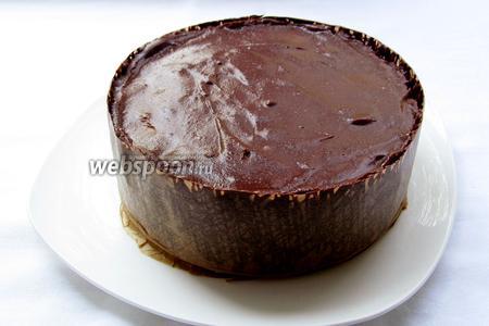 Через 5 минут обернуть торт лентой по всему диаметру, шоколадом внутрь, слегка прижать и разгладить. Поставить торт в холодильник на пол часа.