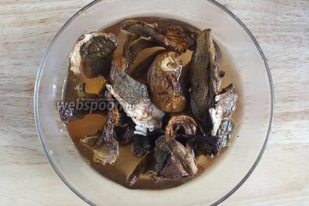 Залейте белые грибы 1 стаканом тёплой воды и оставьте на 15 минут. Включите духовку на 180°C.