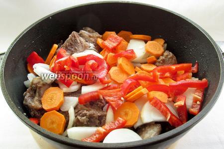 К обжаренному мясу добавить нарезанный лук, морковь и болгарский перец. Обжарить 3 минуты.