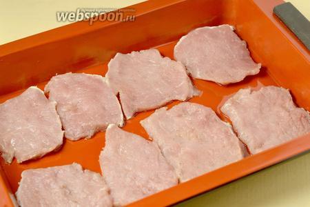 Смазать форму для запекания маслом, уложить пластинки свинины.