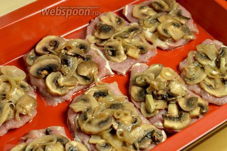 На каждый кусочек мяса выложить шампиньоны с луком.