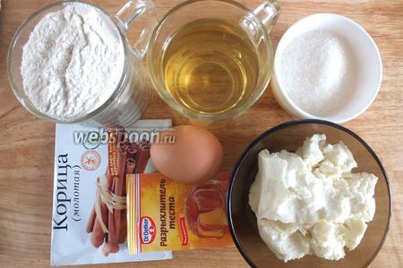 Подготовьте следующие ингредиенты: творог, пшеничную муку, рафинированное растительное масло, сахар и ванильную сахарную пудру, щепотку соли, куриные яйца, корица.