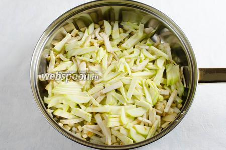 Добавить нарезанные баклажаны и кабачки к луку. Перемешать. Тушить в течение 5-7 минут под крышкой, периодически помешивая.