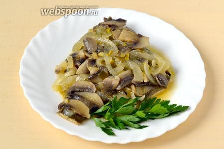 Выкладываем рыбу на тарелки, сверху кладём грибы с луком и поливаем маринадом. Блюдо можно посыпать нарезанной петрушкой или положить её целыми веточками.