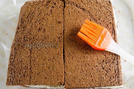Накрыть шоколадный слой двумя половинками коржа, совместив их рядом. Пропитать второй корж.