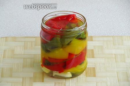 На дно стерилизованных банок ёмкостью 0,5 л положить разрезанный чеснок, плотно уложить перец вместе с зеленью петрушки и залить маринадом.