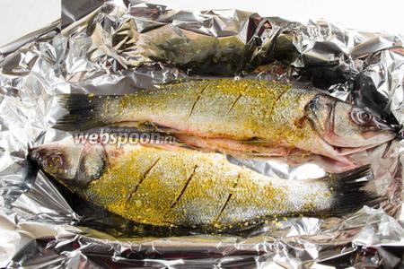 На противень расстелить фольгу. Рыбу натереть специями и солью. Выложить на противень.