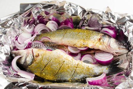 Лук нарезать крупно. Часть вложить внутрь рыбы, остальной лук разложить на противне.