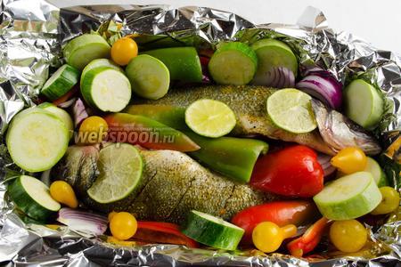 Выложить нарезанные овощи вокруг рыбы. Взбрызнуть соком лайма, используя пару долек, рыбу. Полить оливковым маслом овощи и рыбу.