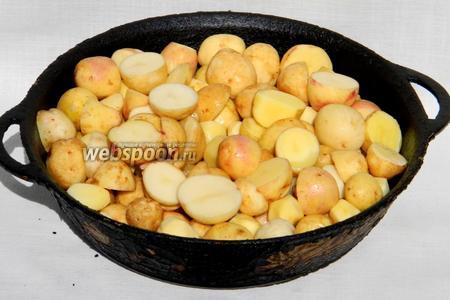 Раскаляем в толстостенной сковороде масло. Высыпаем подготовленный молодой картофель. Жарим под крышкой на среднем огне в течении 20 минут, периодически помешивая.