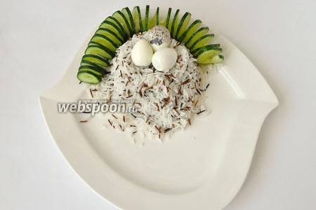 На блюдо для подачи выложим горкой рис. Сделаем сверху углубление и выложим чищеные яйца. Оформим огурцом, резанным спиралькой.