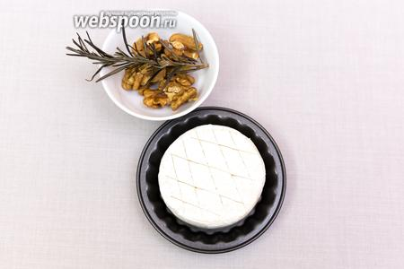 На дно формочки кладём несколько иголочек розмарина, сверху на него — шайбочку сыра Бри. На сыре сделаем неглубокие надрезы.
