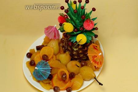 Выкладываем охлаждённые фрукты на блюдо, для оформления размещаем там же подготовленный «подсвечник» из ананаса, украшенный ягодами и декоративными шпажками. Подаем с мороженым, шампанским или игристым вином.