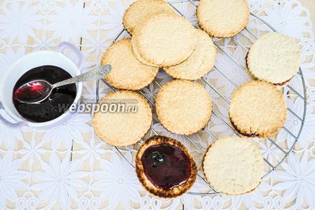 Соединить печенья, смазав их с одной стороны густым вареньем.