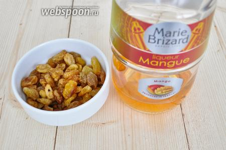 Изюм перебрать, промыть и замочить в манговом ликёре. Можно использовать любой цитрусовый ликёр. Если готовите для детей, используйте сироп от консервированных фруктов или воду.