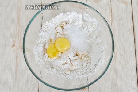 Масло порубить с мукой и солью, добавить сахар и желтки.