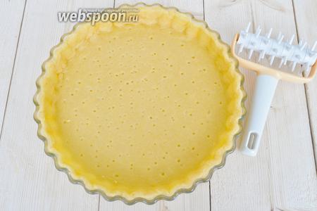 Пройтись по тесту валиком с колючками, чтобы тесто не вздувалось. Можно наколоть вилкой. Теста хватает на форму диаметром 27 см тонким слоем.