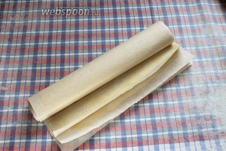 Готовые листы теста переложить пергаментом и свернуть рулончиком.