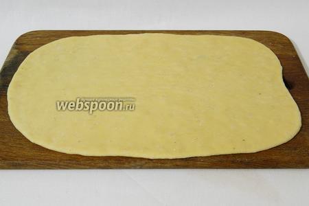 Подошедшее тесто раскатываем в тонкий пласт.
