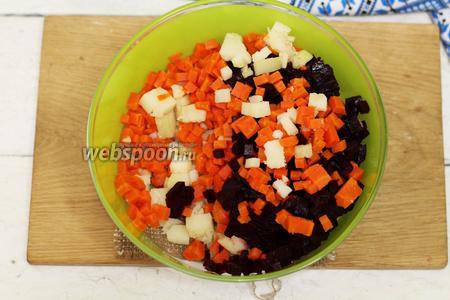 Очищаем от кожицы остывшую морковку и свёклу. Нарезаем небольшими кусочками. Можно воспользоваться тёркой со специальными насадками для нарезки овощей. Добавляем к картофелю.