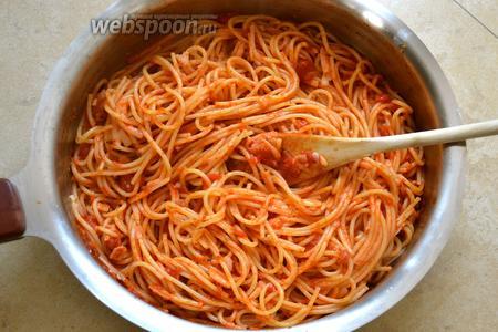 Спагетти смешать с подготовленным томатным соусом, добавить 1/2 натёртого сыра и перемешать.