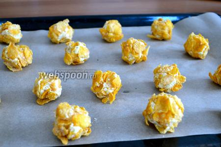 Духовку разогреть до 180°C. Противень застелить пекарской бумагой. Выложить полученные шарики на противень на небольшом расстоянии друг от друга (печенье будет слегка расползаться во время выпечки).  Пока выпекается 1 противень с печеньем, готовим следующую партию. Из указанного количества ингредиентов, печенья получается достаточно много — около 55 штук! Кстати, деткам нравится участвовать не только в поедании этого печенья, но и в процессе его приготовления! ;)