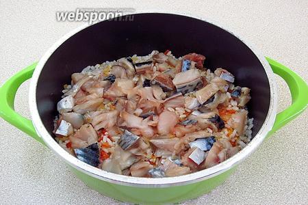 Поверх рисово-овощной массы выложить кусочки рыбы.