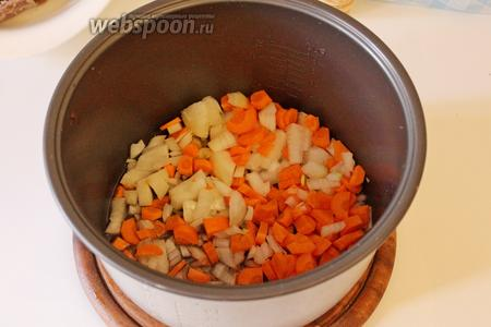 В чашу мультиварки налить масло, выложить лук и морковь. Установить режим «Выпечка»/«Жарка» на 20 минут и готовить 5 минут.
