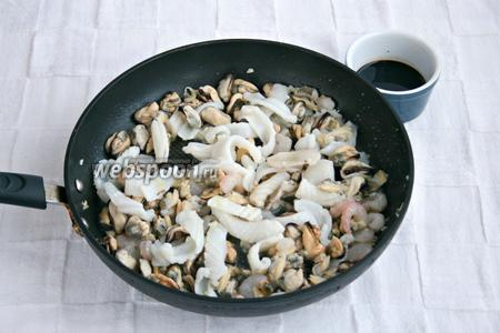 Выложить на сковороду морепродукты и залить соевым соусом.