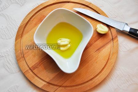 Зубчики чеснока раздавим ножом и поместим их в оливковое масло на 5-10 минут.