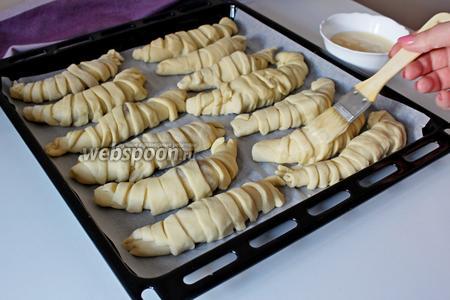 Выложить на противень, застеленный пергаментом, смазать яичным желтком со сливками. Поставить выпекаться при 200°С на 30 минут.