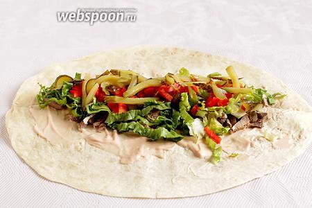 Поверх салата разложить огурцы и сладкий перец.