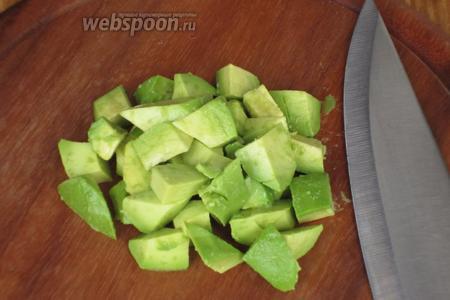 Авокадо очистить от кожуры, разрезать пополам, удалить косточку и нарезать кубиками.
