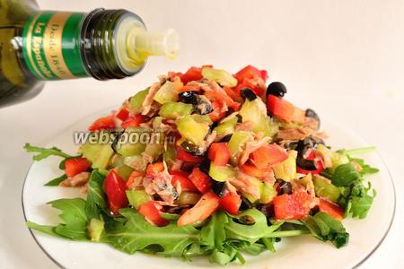 Теперь сервируем и заправляем салат. На тарелку выложить пучок вымытой и обсушенной рукколы. Сверху на эту подушку положить салат. Сбрызнуть всё, немного, лимонным соком и полить оливковым маслом.