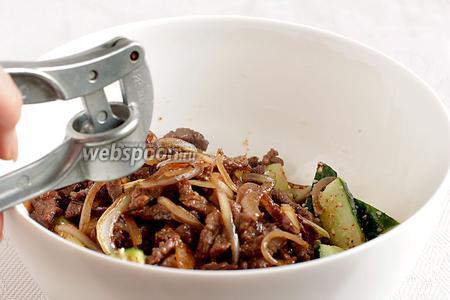 Горячее мясо с луком, вместе с маслом от жарки, добавить к огурцам, выдавить чеснок.