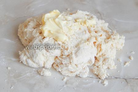 Замешиваем тесто. Когда мука впитает в себя жидкость, перекладываем тесто на стол и частями вводим в него мягкое сливочное масло.