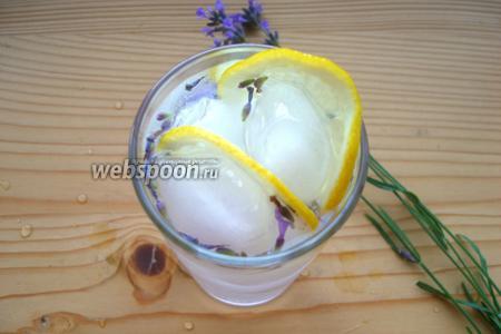 Лимон тонко нарезаем и несколько долек помещаем в хайбол. Ставим веточку лаванды в стакан и немедленно подаём.