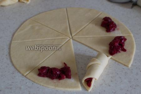 Спустя отведённое время, достаньте тесто, поделите его на 3 равные части, раскатайте каждый кусок, вырежьте из него ровный круг, приложив, например, тарелку. Затем поделите тесто на равные сегменты, как на фото. На широкий край сегмента положите немного вишни и заверните рогалик к центру. Поступите так же со всем оставшимся тестом.