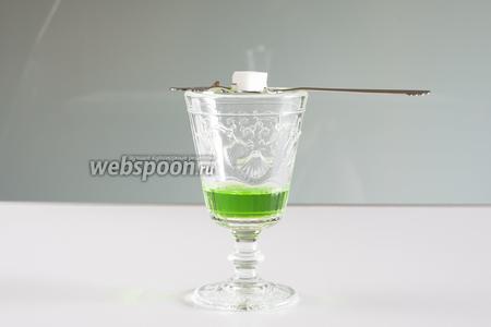 Укладываем поверх бокала специальную ложечку с дырочками, поверх которой укладываем кусочек сахара. Замена ложечке с дырочками — 2 положенные рядом спицы. Или обычная чайная ложка с обычным сахаром, которую вам придётся держать во время следующей операции.