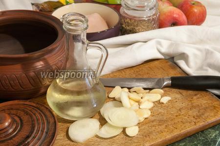 Порежем лук кольцами, чеснок — пластинами. Эти овощи надо поместить на дно политого маслом горшка.