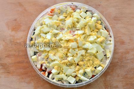 Кладём нарезанные мелко яйца. Разравниваем слой ложкой.