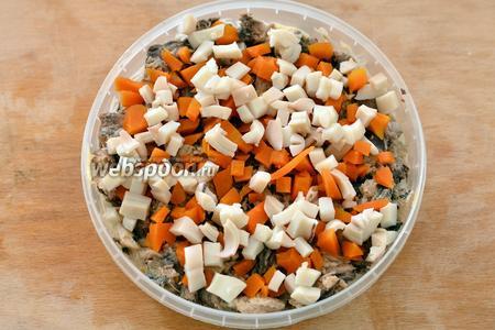 Далее кладём кальмары, нарезанные кубиками, и морковь.