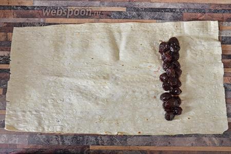Кладём лаваш на ровную поверхность и укладываем в 2 ряда консервированную вишню.