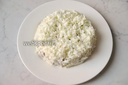 Трём белки на тёрке и полностью ими покрываем салат.